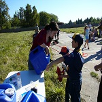 Kayla helps a Scouts refill their water powered vehicles